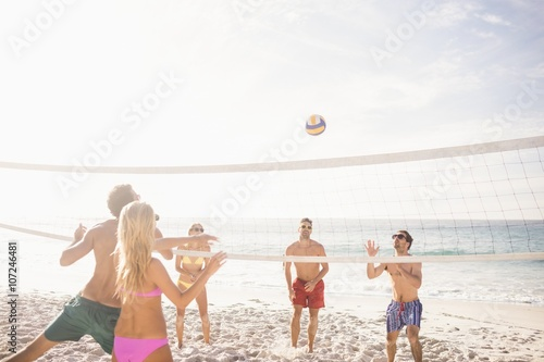 Happy friends playing beach volleyball Canvas Print