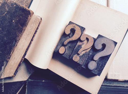 Fotografie, Obraz  Three letterpress question marks on blank pages of vintage book