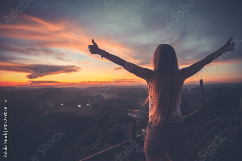 Silhouette of the woman spreading arms with her thumbs up, standing high on the viewpoint with breathtaking view over fields in sunset light Canvas Print