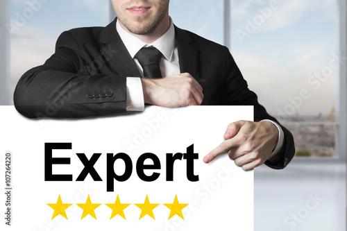 Fotografía  businessman in black suit pointing on sign expert star rating