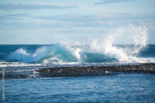 Papiers peints Arctique Ocean waves crashing on icebergs, black sand beach at Jokulsarlon, Iceland