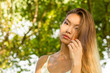 Piękna kobieta dotykająca włosów na tle liści.