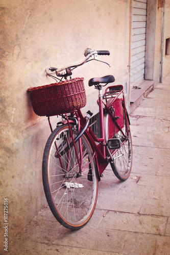 Deurstickers Fiets Vintage red bicycle with wicker basket at the street in Italy