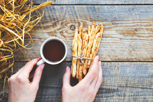Heap Of Bread Sticks With Tea On Wooden Table