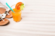 Orange juice and summer accessories on sand with tropical beach background