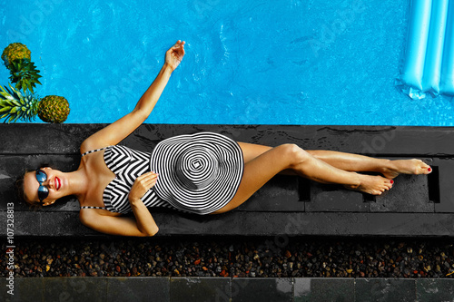 Obraz Woman Summer Fashion. Happy Sexy Smiling Girl With Fit Body, Long Legs, Healthy Skin In Bikini, Sun Hat, Sunglasses Sunbathing By Swimming Pool On Travel Holidays Vacation. Beauty, Wellness, Lifestyle - fototapety do salonu