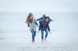 Parents running while carrying children at sea shore