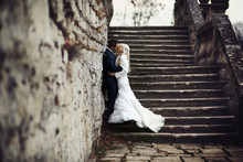 Blonde Bride And Brunette Groom Walking Near  Old Castle