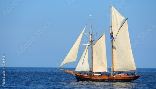 In de dag Schip old historical tall ship (yacht) with white sails in blue sea