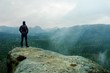 canvas print picture - Hiker on sharp cliff of sandstone rock in rock empires park and watching over misty and foggy spring valley