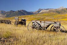 Old Horse-drawn Wagons With The Rocky Mountains In The Background, Near Waterton Lakes National Park, Alberta, Canada