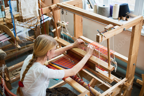 Fotografie, Obraz  The girl in the production process of textiles are handmade on a loom