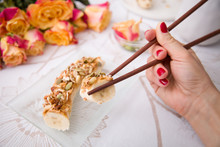 Banana Sushi Servered With Nuts And Granola On A Glass Plate. Hands With Japanese Sticks. Woman Eating Healthy Snack. Flowers And Fruit Breakfast Or Dessert.
