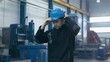 Factory worker in blue uniform is putting his hard hat and goggles on while walking. Shot on RED Cinema Camera.