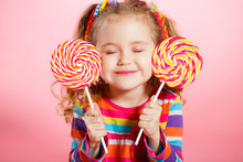 Studio Portrait Of A Beautiful Little Girl With Large Lollipop