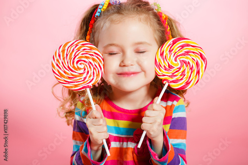 Photographie  Studio portrait of a beautiful little girl with large Lollipop