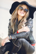 Portrait of a young woman with a beautiful smile,blonde long hair,dressed in a black leather jacket, black hat with large brim and black leather pants,wears dark sun glasses, sitting alone outside