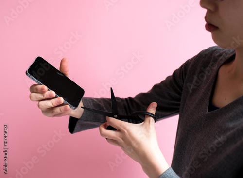 Fotografie, Obraz  スマートフォンをハサミで切る女性