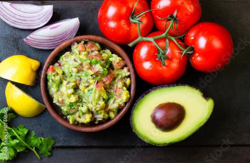 Mexican Latin American sauce guacamole and ingredients - avocado, tomatoes, onion, lemon, cilantro