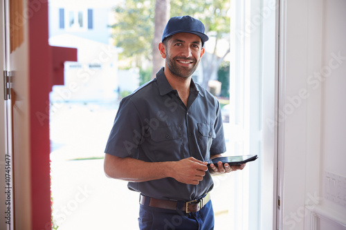 Stampe  Courier Standing At Front Door With Digital Tablet