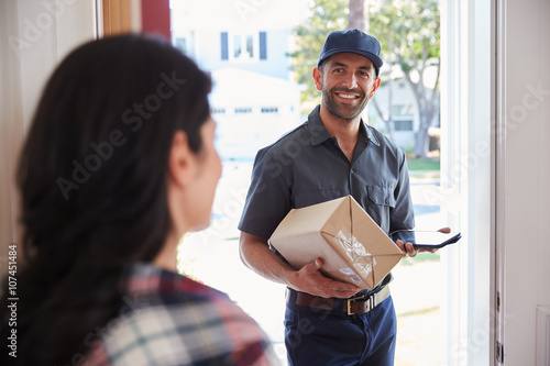 Stampa su Tela  Woman Receiving Package From Courier At Home