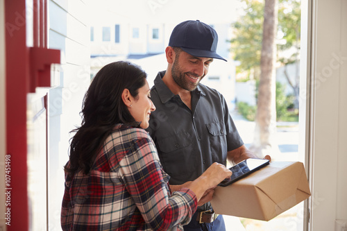 Stampe  Woman Signing For Package From Courier At Home