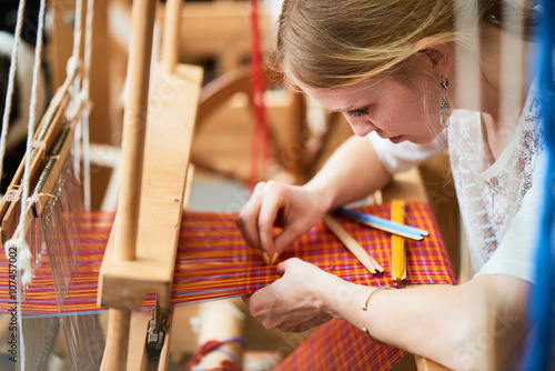 Photo  The girl in the production process of textiles are handmade on a loom