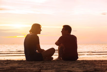Man And Woman On The Beach At Sunset, Young Couple Talking Near The Sea, Dating Or Friendship Concept