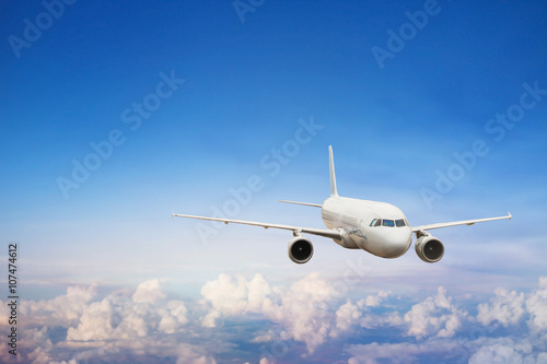 plakat travel by plane, international flight, airplane flying in blue sky above the clouds