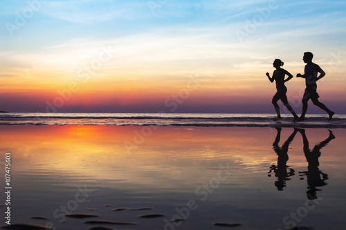 Poster Jogging two runners on the beach, silhouette of people jogging at sunset, healthy lifestyle background with copyspace