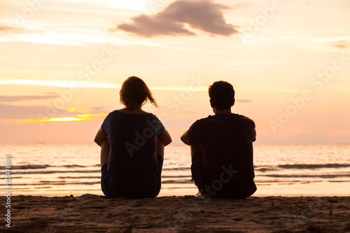 Fotografía  friends sitting together on the beach and watching sunset, friendship concept
