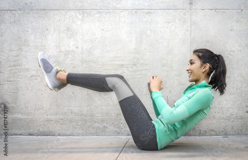 Fotografie, Obraz  Young woman performing core crunch exercise - slight action blur in motion of ac