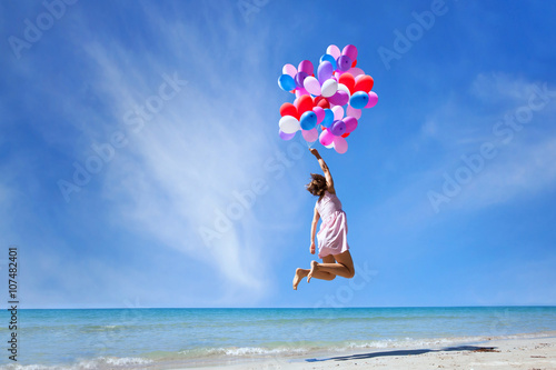Obraz dream concept, girl flying on multicolored balloons in blue sky, imagination and creativity - fototapety do salonu