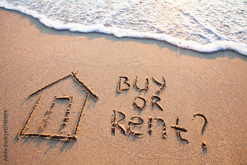 Photo  buy or rent concept, text on the sand, real estate