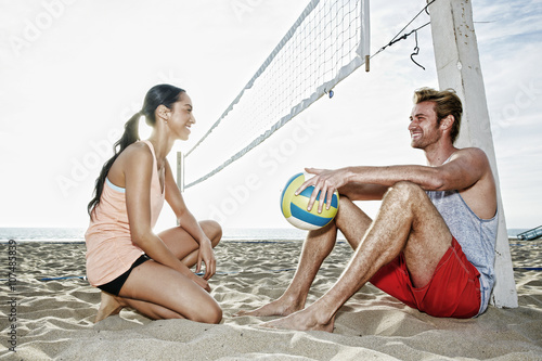 Friends talking near volleyball net on beach Poster