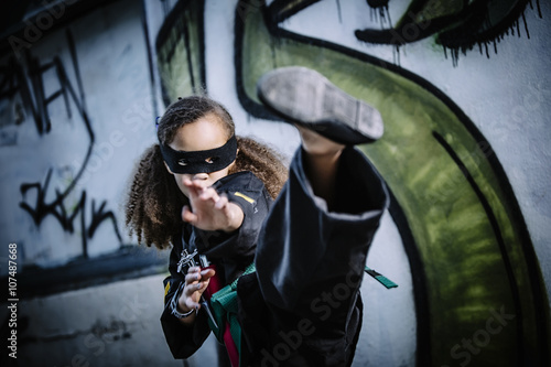 Mixed race girl kicking in martial arts uniform and mask