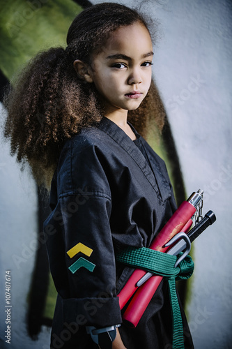 Mixed race girl wearing martial arts uniform with nunchucks