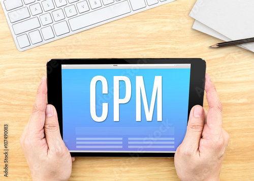Fotografía  Hand holding tablet with CPM (Cost per mille)  word on wood tabl