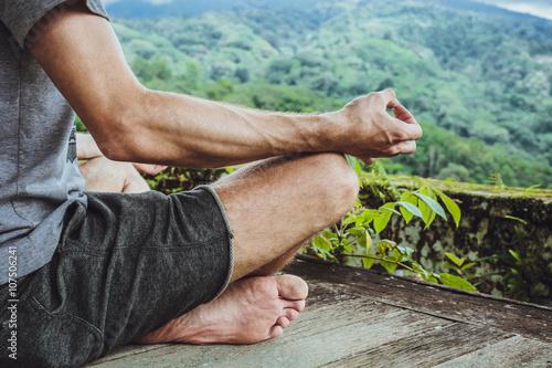 Obraz na plátně  Mladý módní muž meditace v altánku na pozadí