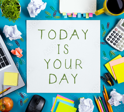 Today is your day. Office table desk with supplies, white blank note pad, cup, pen, pc, crumpled paper, flower on blue background. Top view © projectio