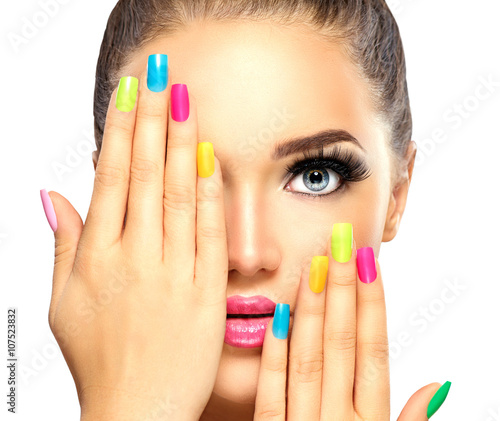 Valokuva Beauty girl face with colorful nail polish. Manicure and makeup