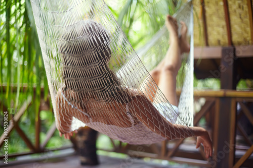 Deurstickers Young woman relaxing in hammock in a tropical resort.back view
