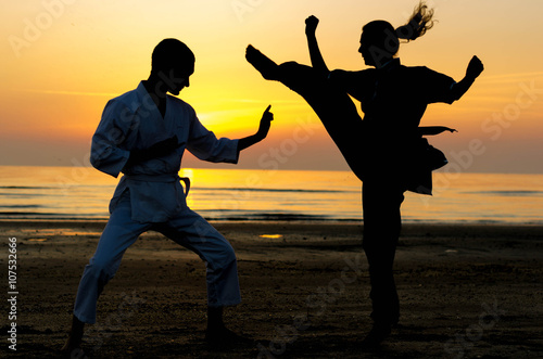 Fotografering  Artial marts fight between master and his pupil at the beach during the sunrise