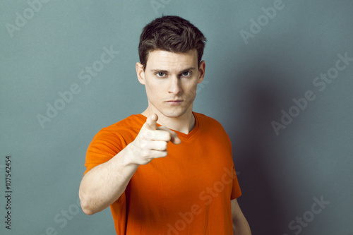 Photo blaming concept - threatening handsome young man showing something or someone wi