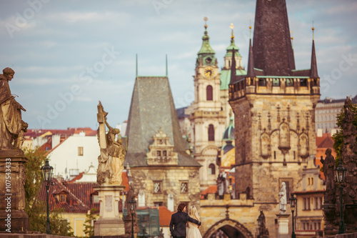 Foto op Plexiglas Praag Romantic newlywed couple on honeymoon, hugging on bridge in Prag