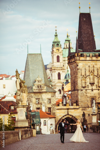 Foto op Plexiglas Praag Happy romantic brid & groom holding hands on bridge in Prague