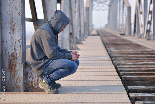 Photo Thinker teenager in depression sitting down on the bridge at the