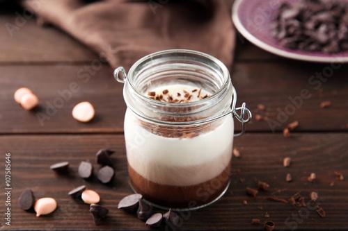 Foto op Aluminium Milkshake Delicious vanilla-chocolate mousse on wooden background, close up