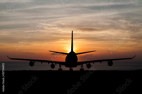 Tuinposter Silhouette of passenger aircraft, airline on beautiful sunset