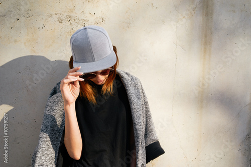 Fotografia  Female model wearing a black blank cap and sunglasses looking away